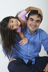 Smiling Hispanic girl leaning on father