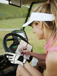 Caucasian woman in golf cart writing on score card