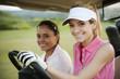 Women driving golf cart on golf course