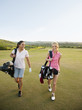 Women carrying golf bags on golf course