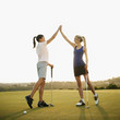 Women golfers high fiving on golf course