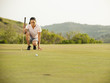 Mixed race woman checking ground on golf course