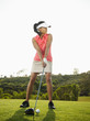 Mixed race woman preparing to swing golf club on golf course