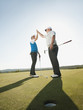 Caucasian golfers high fiving on golf course