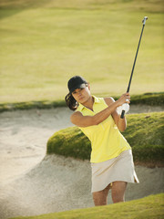 Mixed race woman hitting golf ball out of bunker