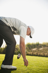 Caucasian golfer placing ball on golf course