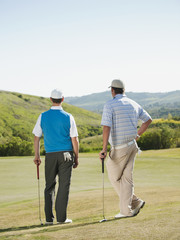 Caucasian men playing golf together on golf course