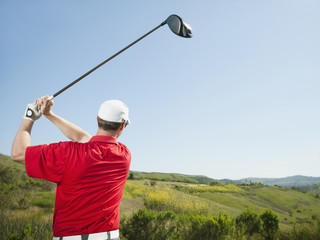 Caucasian golfer swinging golf club