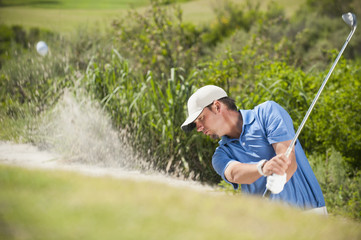 Caucasian golfer hitting ball out of bunker