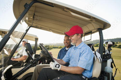 Men driving golf carts on golf course