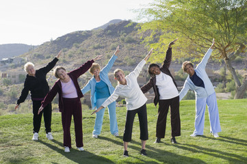 Women taking exercise class outdoors