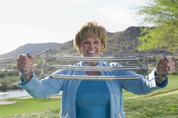 Caucasian woman using stretching exercise equipment outdoors