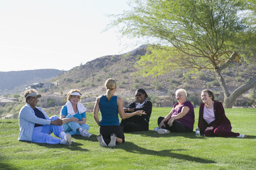 Exercise teacher talking to women sitting in grass