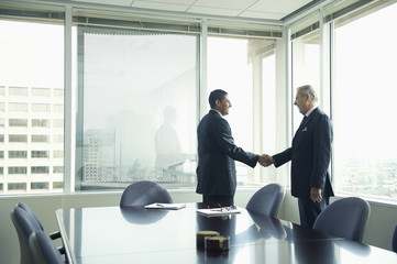 Hispanic businessmen shaking hands in conference room