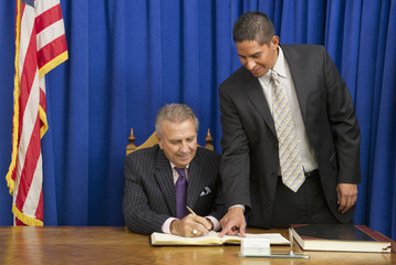 Hispanic businessman showing politician where to sign book