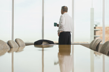 Hispanic businessman drinking coffee in conference room