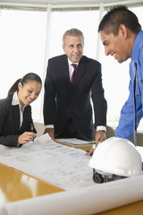 Business people looking at blueprints in conference room