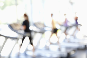 Defocused view of people on treadmills in health club