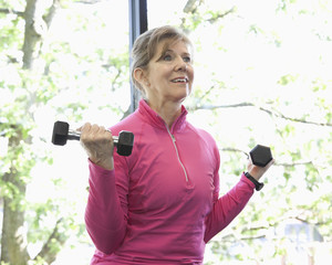 Woman lifting weights in health club