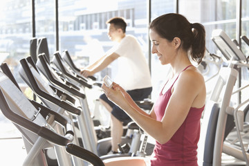 Woman on treadmill text messaging on cell phone