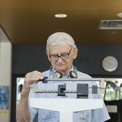 Senior man weighing himself in health club