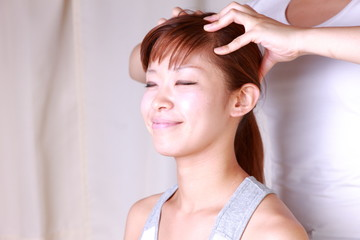 young japanese woman getting a head massage
