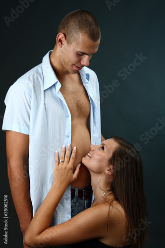 Guy with undone shirt and his girlfriend kneeling before him