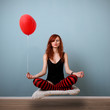 Levitation portrait of red caucasian girl with balloon.