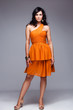 elegant woman in orange dress full body shot