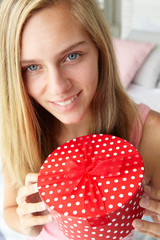 Teenage girl holding gift box