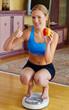 Frau mit Personenwaage und Apfel