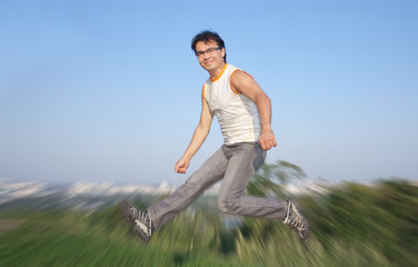 Happy young man jumping in air, blurred background