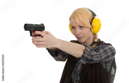 woman in protective receivers aiming pistol at shooting range