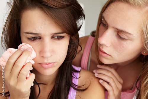 Teenage girl comforting tearful friend
