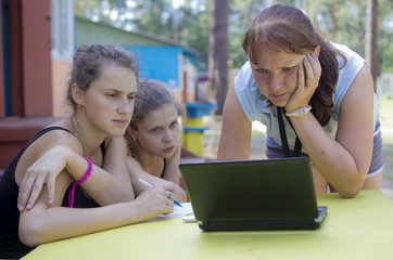 Three girls sit before the notebook and discuss something