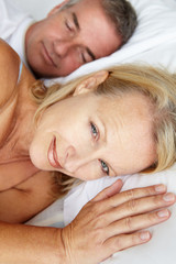 Mid age couple in bed woman awake
