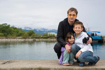 Мужчина с детьми на озере