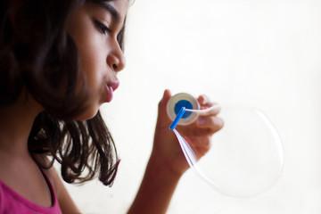 bambina che fa bolla di sapone