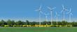 Leinwanddruck Bild - Windkrafträder in einem Rapsfeld hinter einer Allee