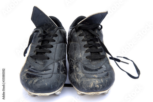 Dirty black leather football soccer boots isolated on white