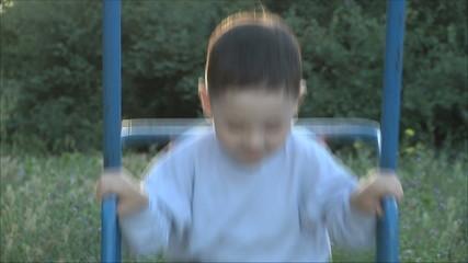 Маленький мальчик катается на качелях 2