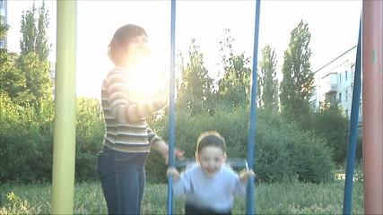 Мама качает мальчика на качелях