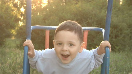 Маленький мальчик катается  на качелях 1