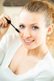 Young woman applying mascara with lash brush poster