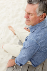 Senior man sitting by beach