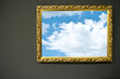 Antique empty golden frame with sky on grunge wall