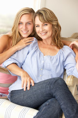 Mid age woman and teenage daughter at home