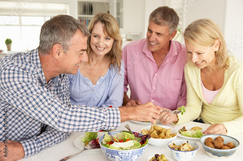 Mid age couples enjoying meal at home