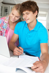 Teenage boy and girl doing homework with laptop