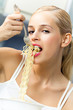 Happy smiling young woman eating spaghetti